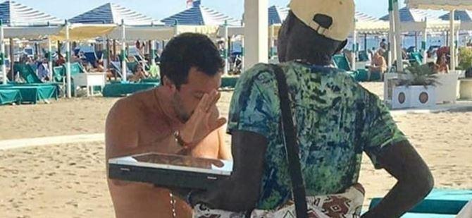 Salvini sulla spiaggia alle prese con un venditore ambulante